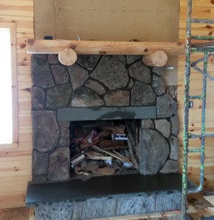 Progress photo of the fireplace fieldstone veneer, pine log mantle, bluestone hearth and header.